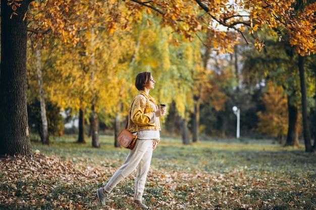 Jeune femme dans un parc en automne, boire du café