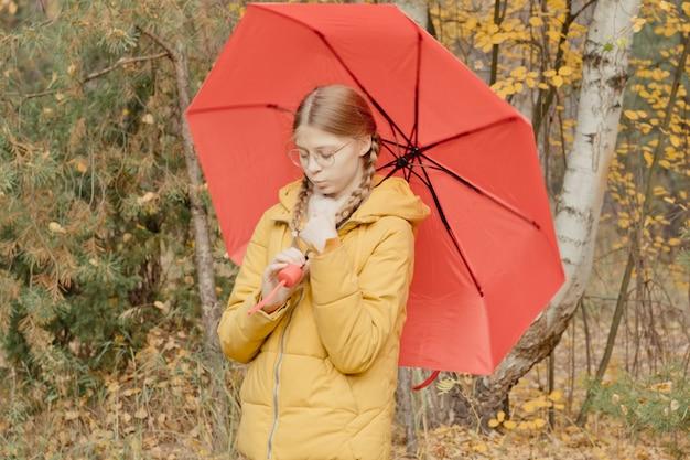 Jeune femme dans un parc d'automne avec un parapluie rouge, tournant et tenant un parapluie, promenade d'automne dans un parc jaune d'octobre