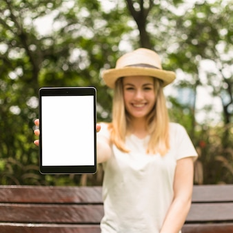 Jeune femme dans le parc montrant une tablette avec écran blanc