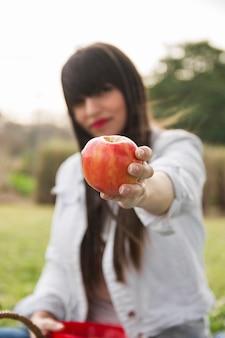 Jeune femme, dans parc, projection, pomme rouge