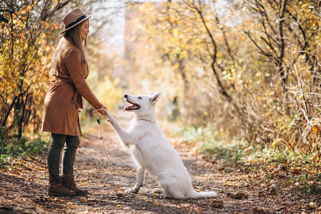 Jeune femme dans un parc avec son chien blanc