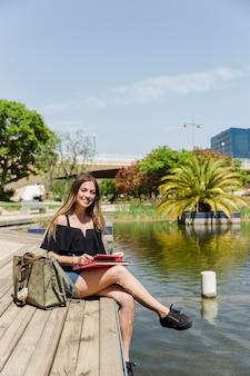 Jeune femme dans le parc avec tablette et livre