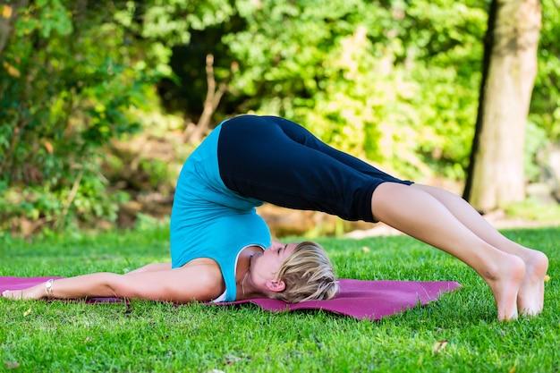 Jeune femme, dans, parc ville, faire, yoga, ou, échauffement, pour, exercice