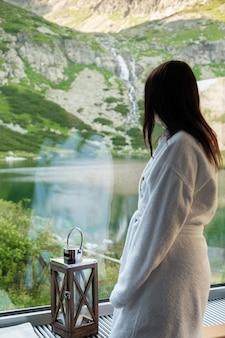 Jeune femme dans un peignoir blanc debout devant la fenêtre et profiter de la nature. spa et