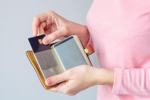 Jeune femme dans un pull rose met une carte de crédit dans un portefeuille