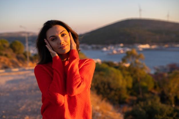 Jeune femme dans un pull rouge à un magnifique coucher de soleil sur la montagne