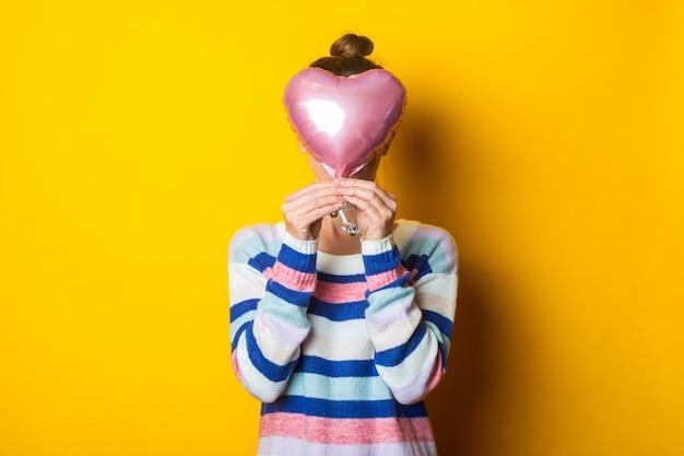 Jeune femme dans un pull se cache derrière un coeur de ballon à air sur fond jaune. composition de la saint-valentin.