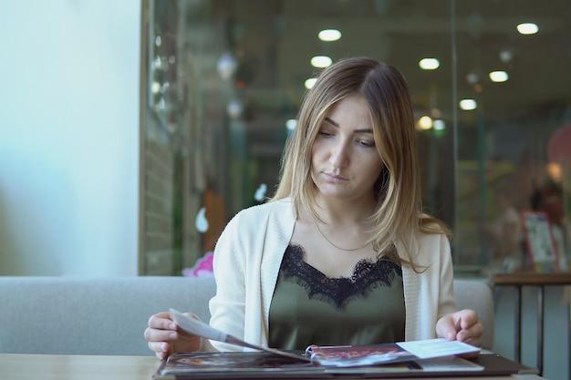 Jeune femme dans un restaurant avec le menu en mains.