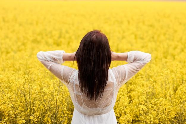 Jeune femme dans une robe blanche dans un champ avec des fleurs de viol