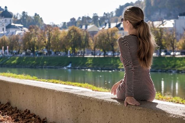Jeune femme dans une robe décontractée et des lunettes de soleil se reposant à l'extérieur par une chaude journée d'automne.