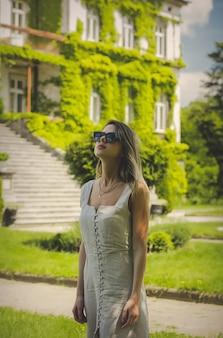 Jeune femme, dans, robe, et, lunettes soleil, à, vieux bâtiment