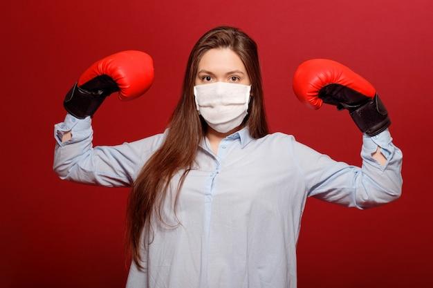 Jeune femme, dans, rouges, gants boxe, sur, mur rouge, dans, protecteur, masque médical