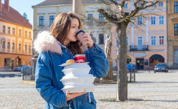 Jeune femme dans la rue avec un manteau avec des boîtes à lunch et livraison à emporter de café et de nourriture.