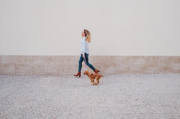 Jeune femme dans la rue marchant avec son mignon chien cocker. mode de vie à l'extérieur avec des animaux domestiques