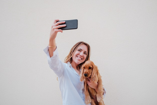 Jeune femme dans la rue avec son chien cocker prendre une photo avec téléphone portable. mode de vie à l'extérieur avec des animaux domestiques