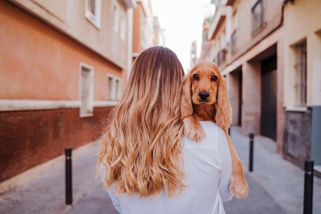 Jeune femme dans la rue tenant avec son mignon chien cocker sur l'épaule. mode de vie à l'extérieur avec des animaux domestiques