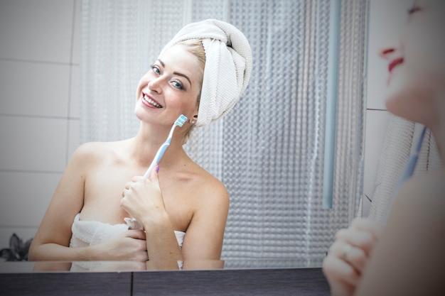 Jeune femme dans la salle de bain se brosser les dents avec une brosse à dents avec un sourire sur mon visage dans une serviette
