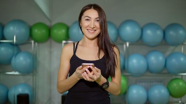 Jeune femme dans la salle de gym, écouter de la musique sur fond de balles de gymnastique.