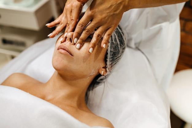 Jeune femme dans un salon de beauté ayant un massage du visage