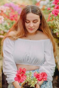 Jeune femme dans une serre avec des azalées