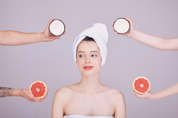 Une jeune femme dans une serviette blanche sur la tête, autour de ses mains avec des fruits.