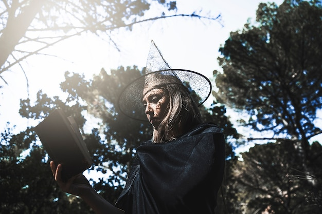 Jeune femme, dans, sorcier, chapeau, et, manteau, lecture, livre, dans, forêt