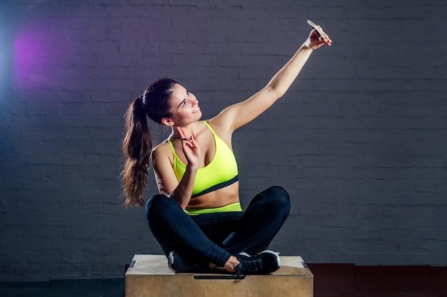Une jeune femme dans un soutien-gorge de sport vert et un pantalon noir est assise sur un tiroir et fait un selfie sur fond de briques noires