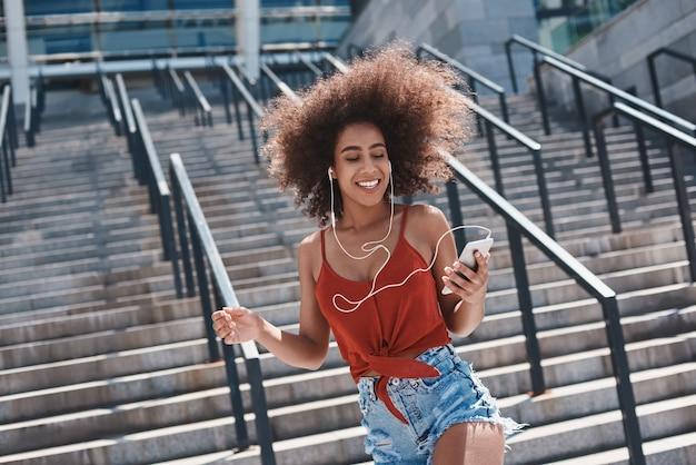 Jeune femme dans le style libre d'écouteurs dans la rue marchant près de s