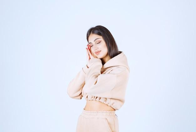 Jeune femme dans un sweat à capuche rose a l'air fatigué et somnolent