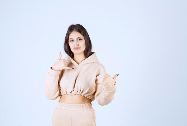 Jeune femme dans un sweat à capuche rose demandant d'appeler