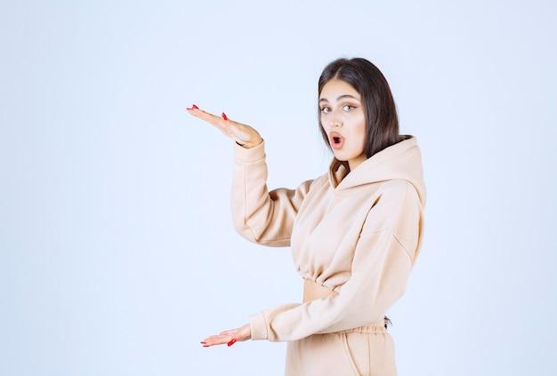 Jeune femme dans un sweat à capuche rose démontrant les mesures estimées d'un objet