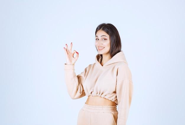 Jeune femme dans un sweat à capuche rose montrant un bon signe de la main