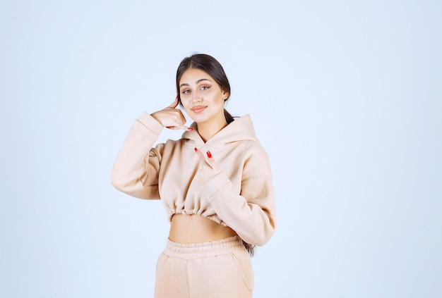 Jeune femme dans un sweat à capuche rose montrant l'indicatif d'appel