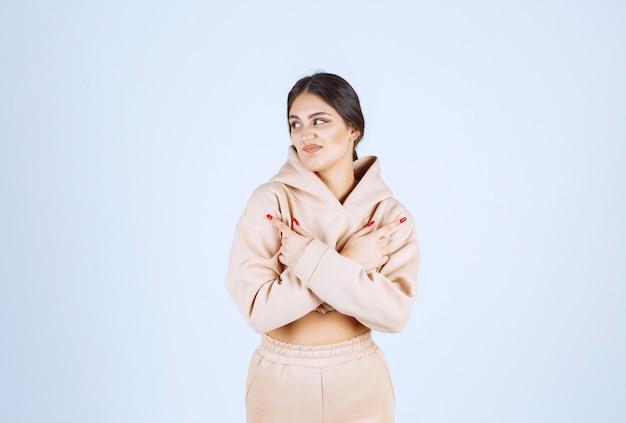 Jeune femme dans un sweat à capuche rose pointant des deux côtés