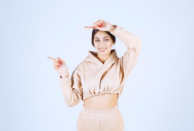 Jeune femme dans un sweat à capuche rose pointant quelque chose sur la gauche