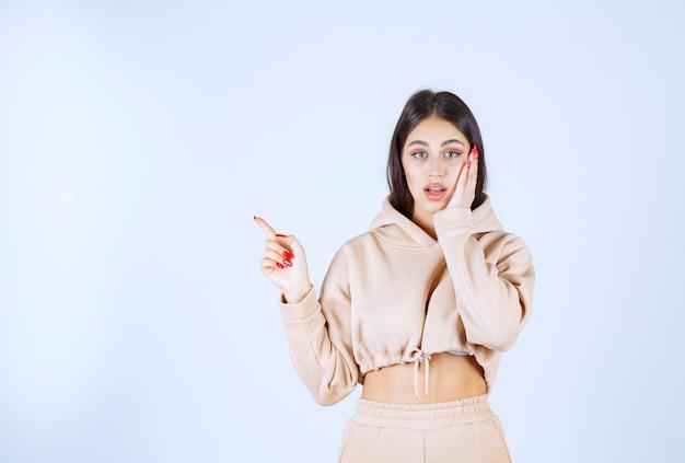 Jeune femme dans un sweat à capuche rose pointant vers la gauche