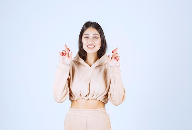 Jeune femme dans un sweat à capuche rose tenant la croix de doigt et souriant