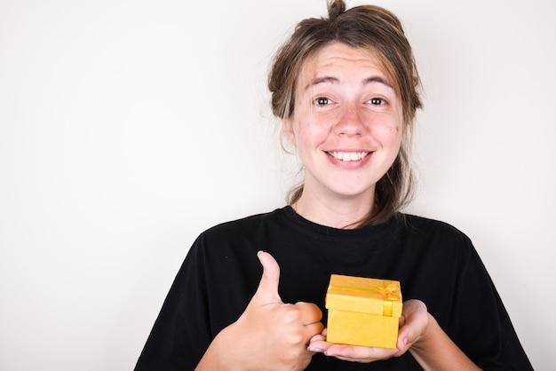 Jeune femme dans un t-shirt noir est heureuse d'accepter un cadeau et de montrer les pouces vers le haut. accepter le concept de cadeaux