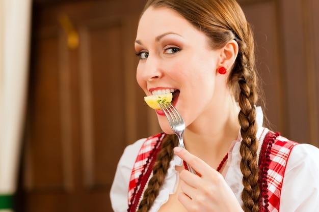 Jeune femme dans un tracht bavarois traditionnel mange au restaurant ou au pub