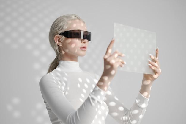 La jeune femme dans des verres tient le gadget futuriste