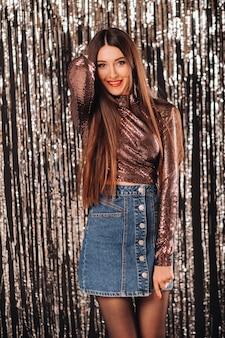Une jeune femme dans une veste brillante posant sur un rideau de guirlandes d'argent