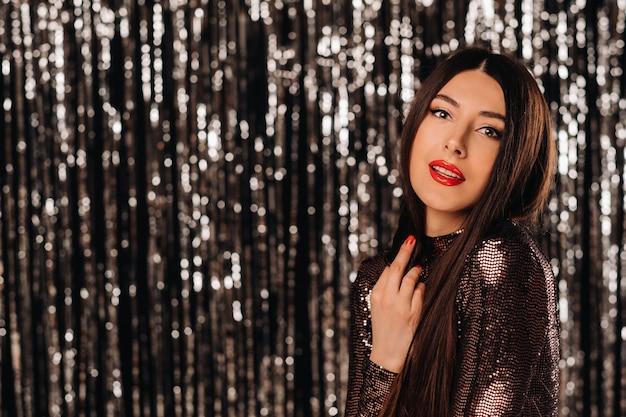 Une jeune femme dans une veste brillante sur rideau de guirlandes d'argent