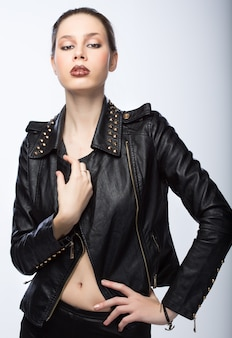 Jeune femme dans une veste en cuir sur fond gris