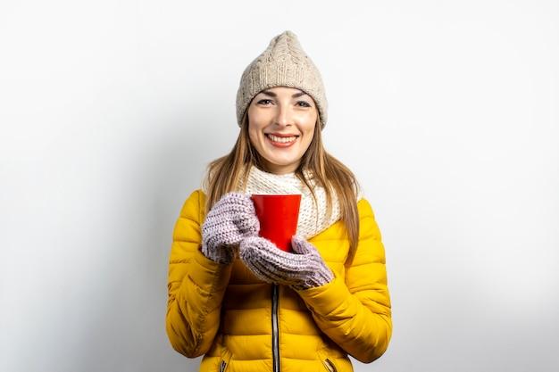 Jeune femme dans une veste jaune et un chapeau tient un verre de café ou de thé sur un fond clair.