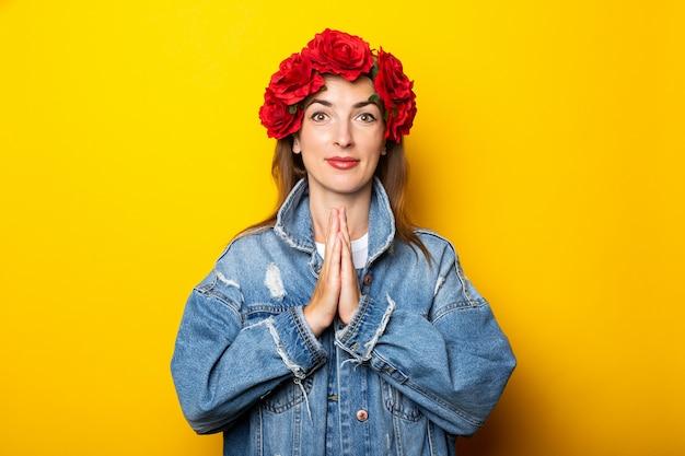 Jeune femme dans une veste en jean et une couronne de fleurs rouges sur sa tête croisa les bras dans une pose de yoga sur un mur jaune.