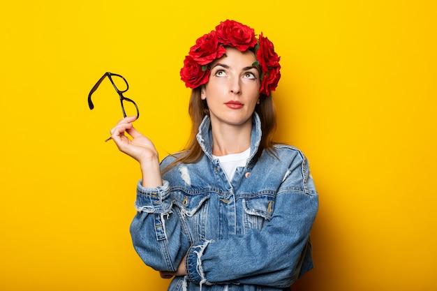 Jeune femme dans une veste en jean et une couronne de fleurs rouges sur sa tête tient des lunettes sur un mur jaune.