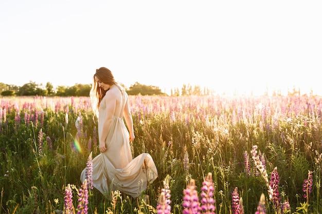 Jeune femme dansant sur un champ de fleurs sauvages avec le lever du soleil sur le fond.