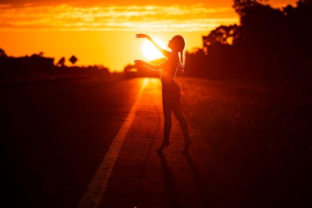 Jeune femme dansant dans le ciel coucher de soleil d'été en plein air. style de liberté des gens.