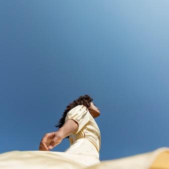 Jeune femme danse sur fond de ciel