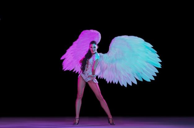 Jeune femme danseuse avec des ailes d'ange en néon sur mur noir